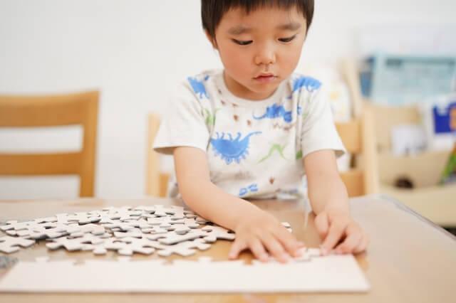 ジグソーパズルで遊ぶ子ども
