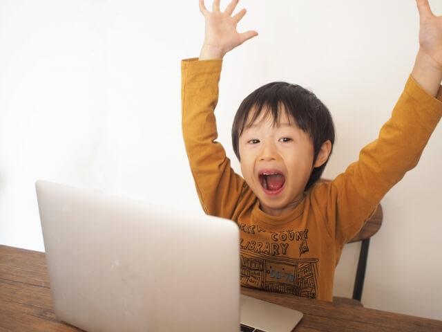 パソコンを前に喜ぶ子ども