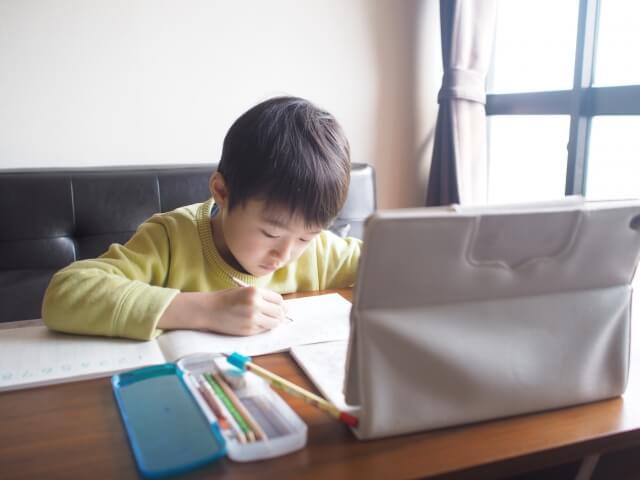 子どもがタブレットの前でノートをとっている様子