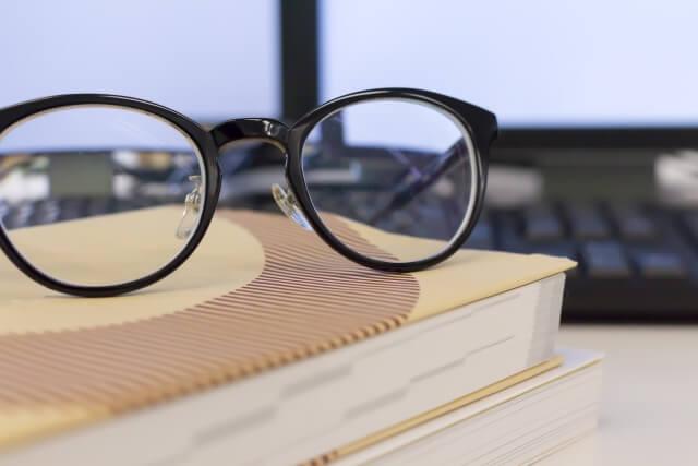パソコンの前の書籍とメガネ