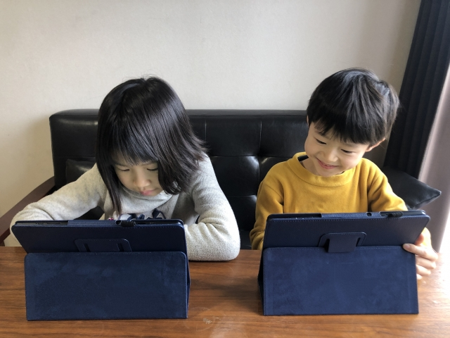 タブレットの前で座る2人の子ども